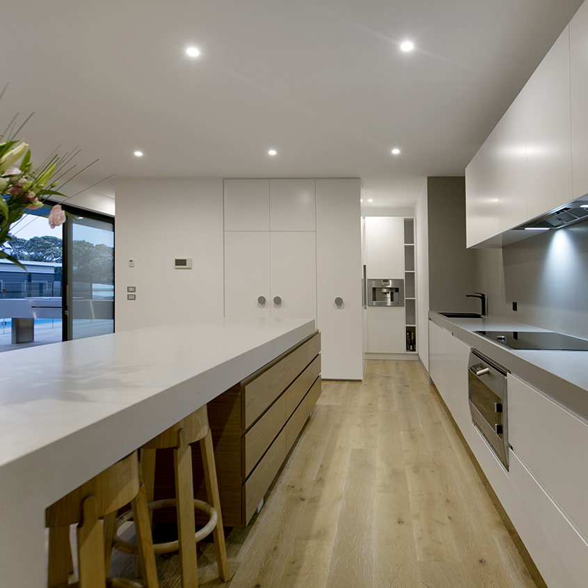 The kitchen's design is simple yet bold, with a sleek rectangular block of timber cabinetry supporting a substantial concrete bench top and water fall end