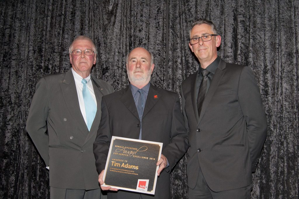 Tim Adams receiving the Ronald Pickford Award for Service Excellence 2018 from Ron Pickford (left) supported by BDAV President, Lindsay Douglas